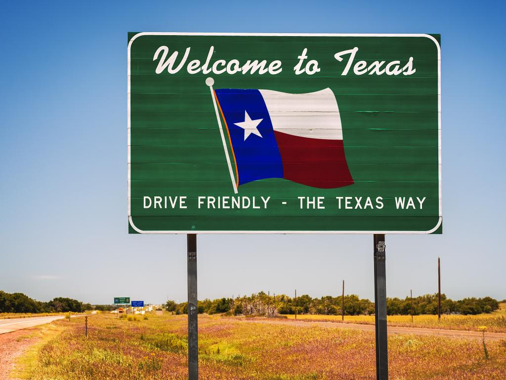 Welcome to Texas road sign at the state border saying Drive Friendly - The Texas Way