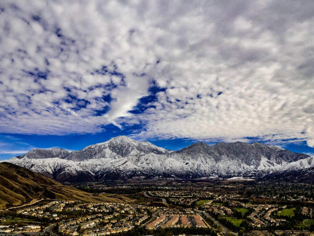 A stunning aerial view of San Gorgonio and Little San Bernardino Mountains covered in snow on a winter day with blue mackerel skies of white and grey clouds.