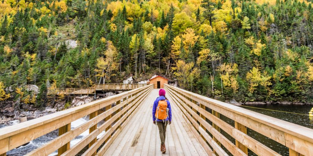 A women walking over a wooden bridge towards a hill covered in trees in a national park in Quebec