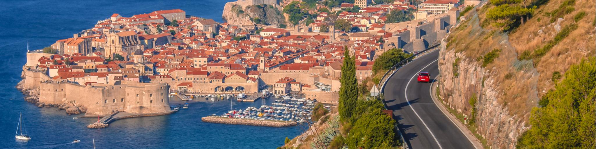 Cars driving along a coastal road in Croatia with the old town of Dubrovnik in the background