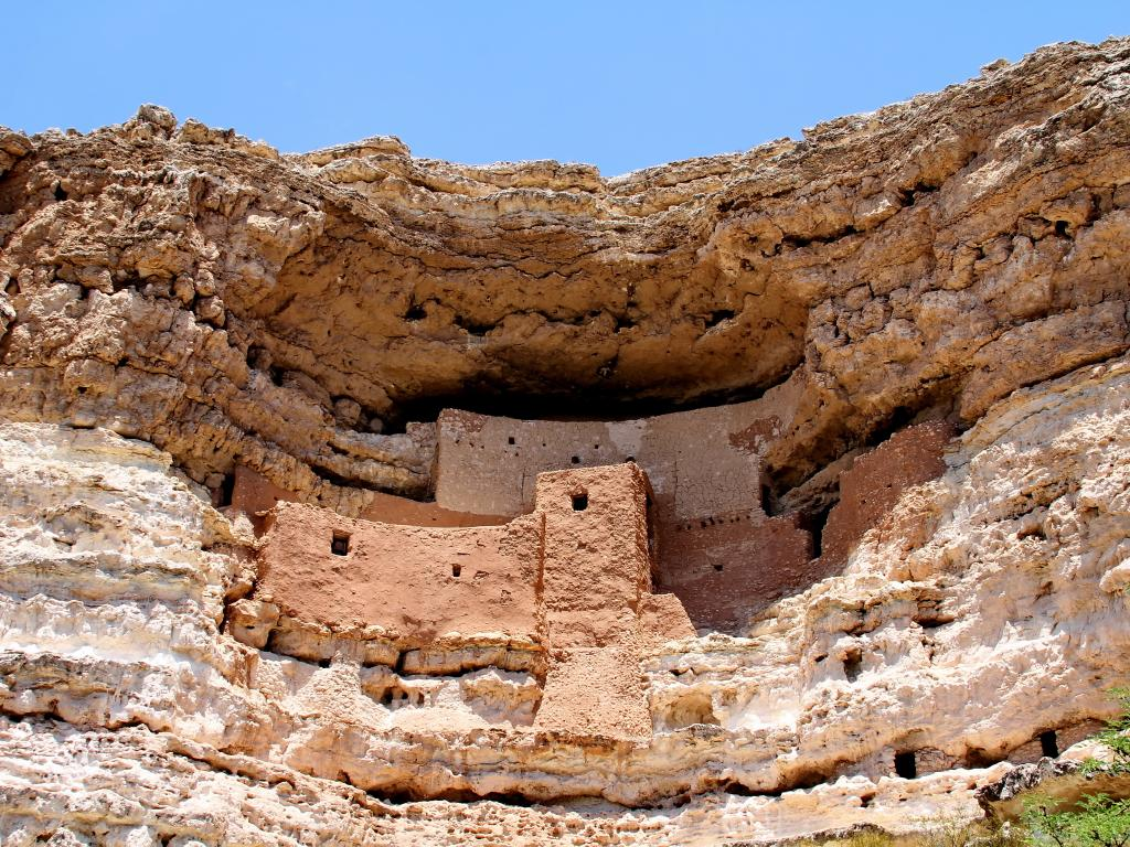 A well preserved Hopi native American cliff dwelling in a mountainside made of stone and dirt framed by the green leaves found in Montezuma Castle National Monument, Arizona