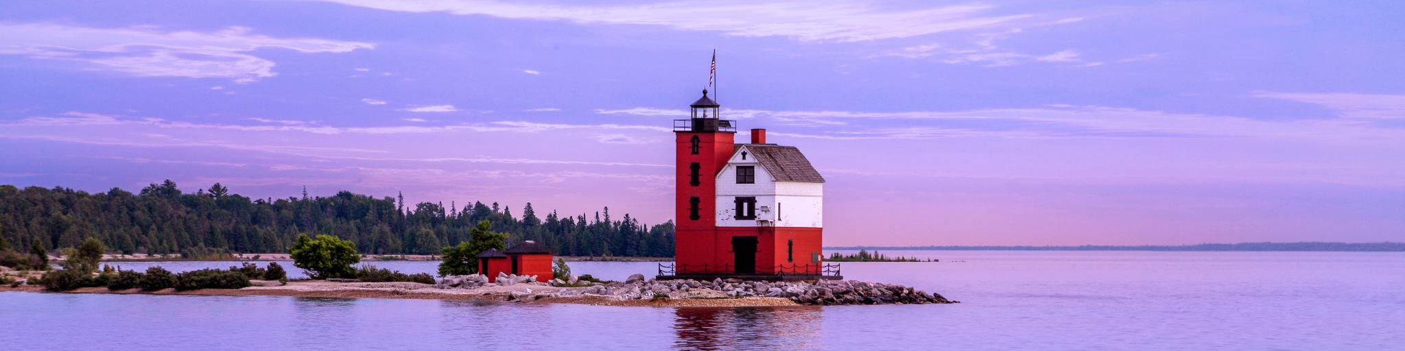 The historic Round Island Lighthouse at the shore of Mackinac Island in a purple and blue sky after sunset with a view of green pine trees at the distance