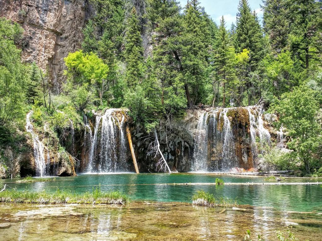Waterfalls and pine forest surrounding Hanging Lake near Glenwood Springs, Colorado.